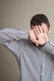 Hombre joven que oculta su cara con las manos Fotos de archivo libres de regalías