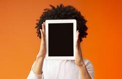 Hombre joven que oculta su cara detrás de la tableta digital imagenes de archivo