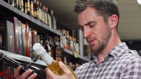 Hombre joven que parece confuso mientras que elige el vino almacen de metraje de vídeo