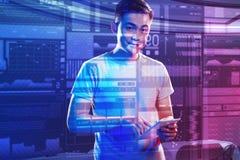 Hombre joven que parece feliz mientras que se coloca con un nuevo dispositivo moderno Imagen de archivo libre de regalías