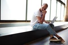 Hombre joven que parece pensativo mientras que trabaja en el ordenador portátil que lo sostiene en las rodillas imágenes de archivo libres de regalías