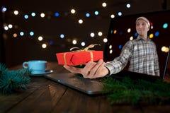Hombre joven que pasa Internet del tiro del regalo de la Navidad foto de archivo