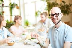 Hombre joven que pasa tiempo en café con los amigos fotografía de archivo libre de regalías