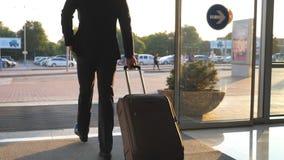 Hombre joven que pasa a través de la puerta automática de cristal del aeropuerto a la ciudad y que tira de la maleta en las rueda almacen de video
