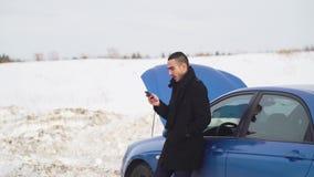 Hombre joven que permanece en la carretera nacional con su coche quebrado y que manda un SMS a un mensaje almacen de metraje de vídeo