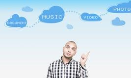 Hombre joven que piensa cómo utilizar la nube Imagen de archivo