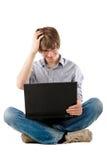 Hombre joven que piensa con la computadora portátil Imágenes de archivo libres de regalías
