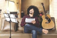 Hombre joven que piensa con la tableta digital Foto de archivo libre de regalías