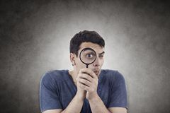 Hombre joven que piensa con una lupa fotos de archivo libres de regalías