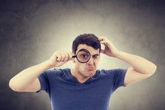 Hombre joven que piensa con una lupa imagen de archivo