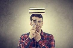 Hombre joven que piensa con una lupa imagen de archivo libre de regalías