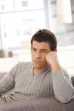 Hombre joven que piensa en el sofá Fotografía de archivo