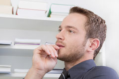 Hombre joven que piensa en la oficina. Imagenes de archivo