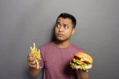 Hombre joven que piensa mientras que sostiene la hamburguesa y las patatas fritas Imagenes de archivo