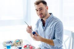 Hombre joven que pinta los huevos de Pascua foto de archivo