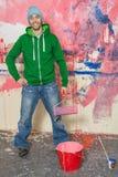 Hombre joven que pinta una pared Foto de archivo libre de regalías