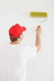 Hombre joven que pinta una pared blanca Imagenes de archivo