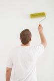 Hombre joven que pinta una pared blanca Foto de archivo