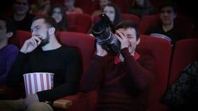 Hombre joven que piratea en el cine almacen de metraje de vídeo
