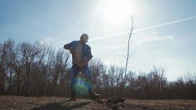 Hombre joven que planta un ?rbol en primavera Alm?cigo joven del ?rbol frutal del sistema del jardinero en el agujero preparado e almacen de metraje de vídeo