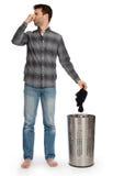 Hombre joven que pone calcetines sucios en una cesta de lavadero Fotos de archivo