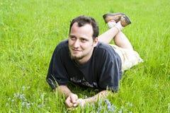 Hombre joven que pone en hierba Imagen de archivo libre de regalías