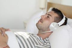 Hombre joven que pone en música que escucha de la cama Foto de archivo libre de regalías