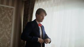 Hombre joven que pone en ventana que hace una pausa de la chaqueta El novio se está preparando para su boda por la mañana metrajes