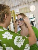 Hombre joven que pone las gafas de sol en novia en tienda de ropa Foto de archivo