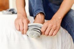 Hombre joven que pone o que saca sus calcetines foto de archivo libre de regalías