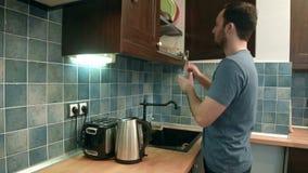 Hombre joven que pone platos lejos en la cocina metrajes