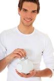 Hombre joven que pone símbolo euro en la batería guarra imagen de archivo