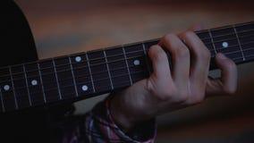 Hombre joven que practica para tocar la guitarra que sueña para ser famoso, lecciones de música, carrera almacen de video
