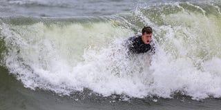 Hombre joven que practica surf Fotografía de archivo libre de regalías
