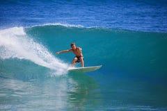 Hombre joven que practica surf en el pánico de la punta Fotos de archivo libres de regalías