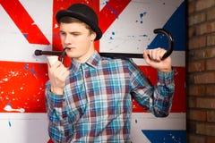 Hombre joven que presenta con el tubo que fuma y el bastón Imagen de archivo