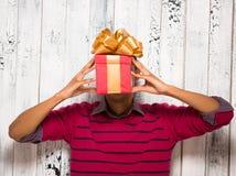 Hombre joven que presenta con un presente en estudio Fotografía de archivo libre de regalías