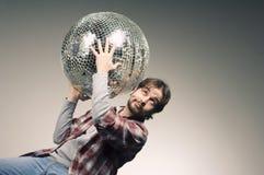 Hombre joven que presenta con una bola de discoteca Fotos de archivo libres de regalías