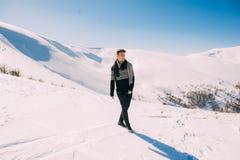 Hombre joven que presenta contra un fondo de montañas nevosas Fotografía de archivo