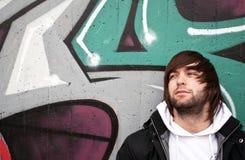 Hombre joven que presenta delante de la pared de la pintada Fotos de archivo