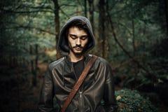 Hombre joven que presenta en el bosque Fotografía de archivo
