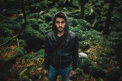 Hombre joven que presenta en el bosque Foto de archivo
