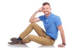 Hombre joven que presenta en el piso Foto de archivo libre de regalías