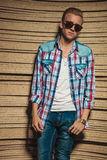 Hombre joven que presenta en gafas de sol que llevan del estudio de madera Fotografía de archivo libre de regalías