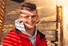 Hombre joven que presenta en la chaqueta roja cubierta con la sombra hermosa Fotos de archivo