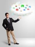 Hombre joven que presenta la nube con los iconos coloridos y los símbolos del app Imagen de archivo