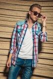 Hombre joven que presenta mientras que fija sus gafas de sol Imagen de archivo libre de regalías