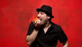 Hombre joven que presenta y que come la manzana Imagen de archivo libre de regalías