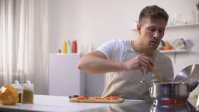 Hombre joven que prueba el alimento cocido con la expresión asqueada de la cara, el hacer muecas divertido metrajes