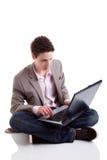 Hombre joven que pulsa y que mira la pantalla de la computadora portátil Imagenes de archivo